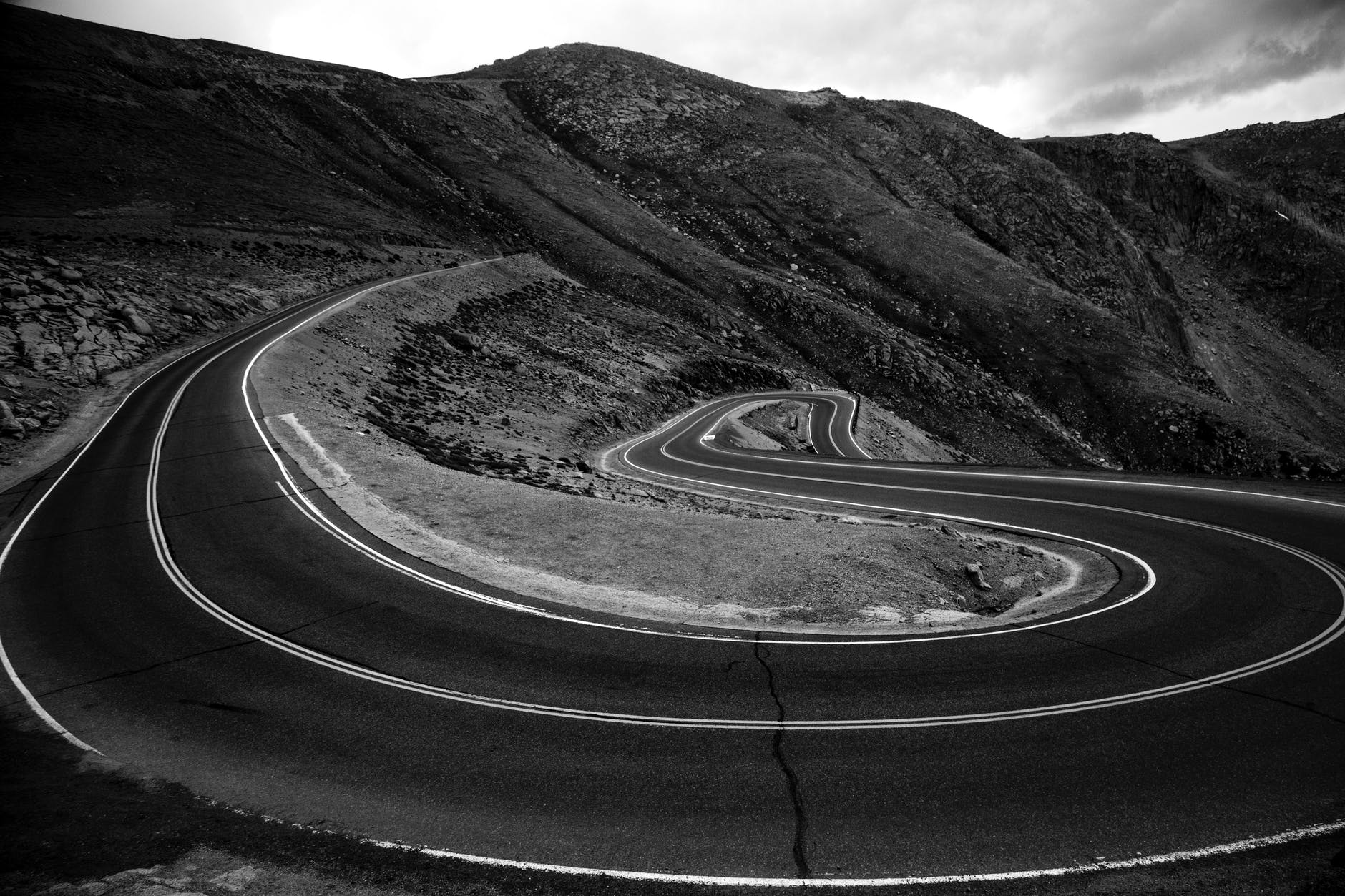 grayscale photo of a road in the middle of a mountain